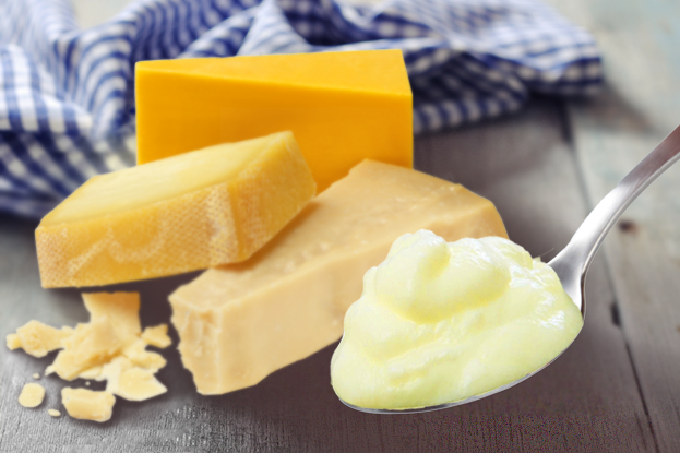 Cream-on-spoon-cheese-background
